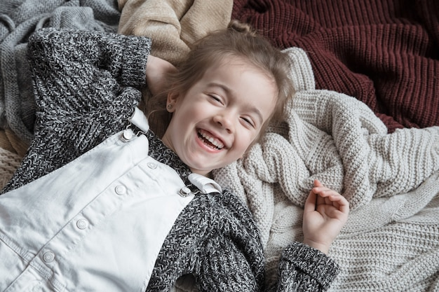 Cute little fun girl in a knitted sweater.