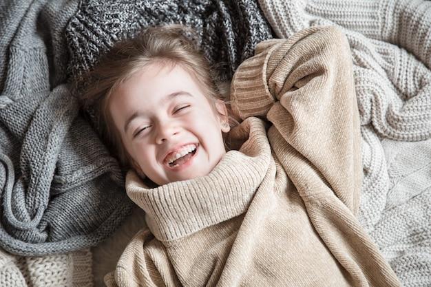 Bambina sveglia divertente in un maglione lavorato a maglia.