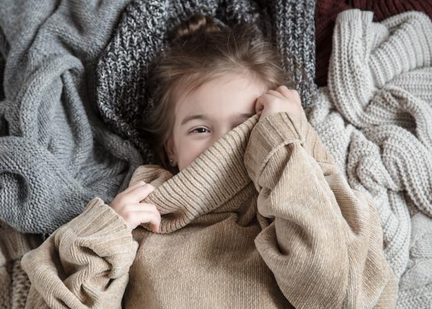 Bambina sveglia divertente in un maglione lavorato a maglia
