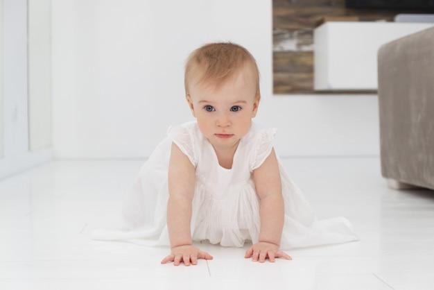 Милая маленькая забавная кавказская белокурая девочка в белом платье, ползая на четвереньках по полу дома