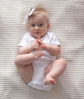 かわいい小さな面白い白人のブロンドの女の赤ちゃん、頭にピンクの弓、笑顔、カメラを見て、自宅の装飾的な枕の表面にobベッドを横にしています