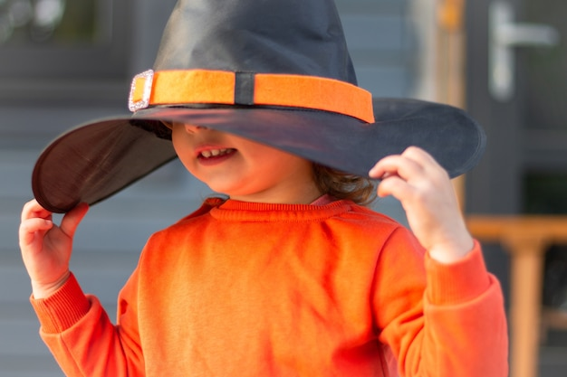 Cute little girl 2-3 in a big witch hat on the terrace of a wooden gray house