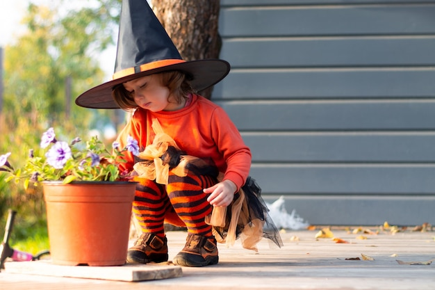 A cute little girl 2-3 in an orange and black halloween witch costume sits next to flowers on the terrace of gray house