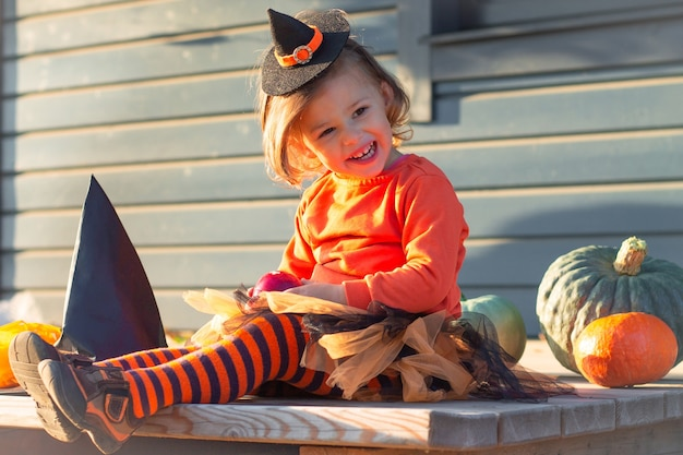 A cute little girl 2-3 in an orange and black witch costume sits next to pumpkins on the terrace of a wooden gray house