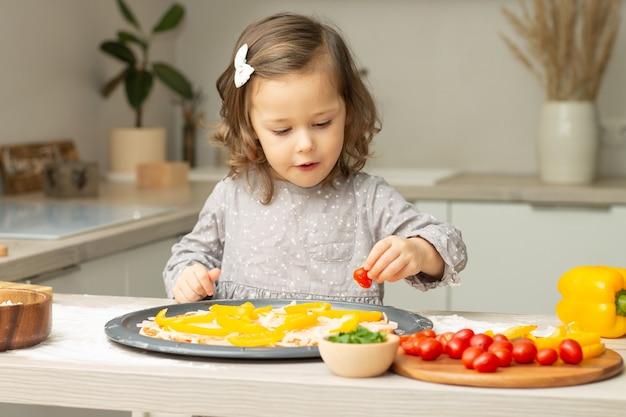 부엌에서 피자를 요리하는 회색 드레스에 귀여운 소녀 2-4. 아이가 피자베이스에 재료를 준비