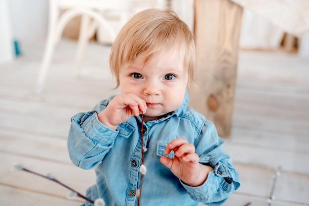 Милая маленькая девочка 2 лет сидит на полу на кухне и смотрит в камеру