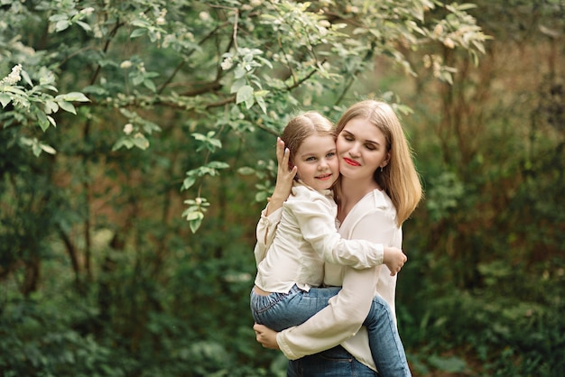 4歳のかわいい女の子と彼女の美しい母親は春に公園を歩いています。
