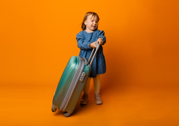 黄色の背景に緑のスーツケースと青いデニムのドレスを着た4歳のかわいい女の子。