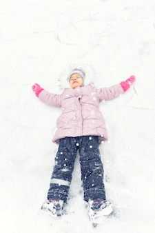 A cute little girl 4 years old in a pink down jacket and a hood lies in a snowdrift rejoicing in the snow. winter fun