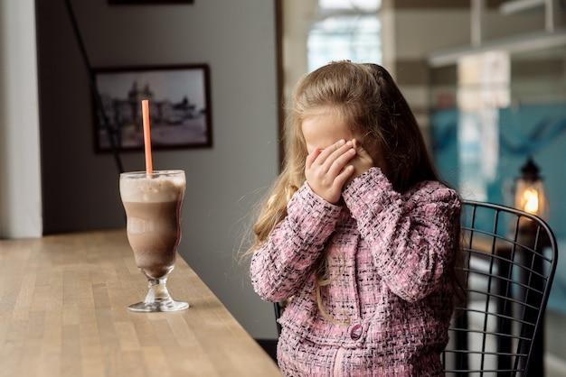 かわいい女の子5歳のカフェでココアを飲む