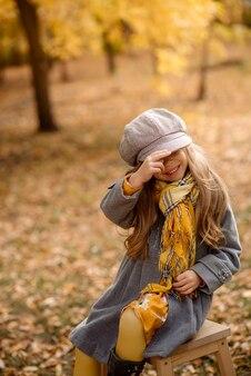 巻き毛の5歳のかわいい女の子が笑い、秋の落ち葉で遊んで