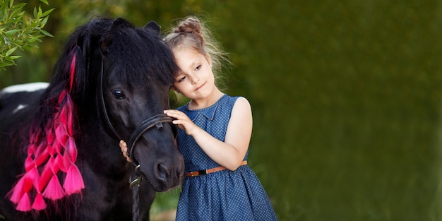 Милая маленькая девочка и черный пони в красивом парке. красивая девушка, обнимая пони. весной или летом. скопируйте место для текста. баннер