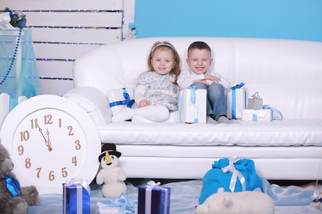 귀여운 작은 소녀와 소년 선물 상자 흰색 소파에 앉아. 크리스마스와 새해를 축하합니다.