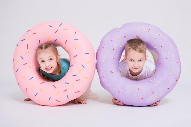 白い背景の上に巨大なドーナツを持つかわいい女の子と男の子