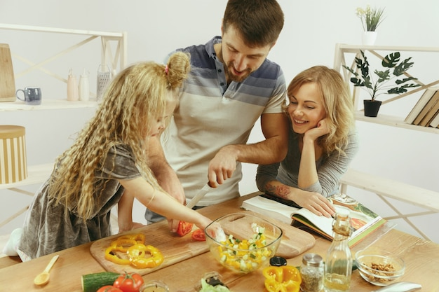 かわいい女の子と彼女の美しい両親は、自宅のキッチンでサラダを作りながら野菜を切って笑っています。家族のライフスタイルの概念