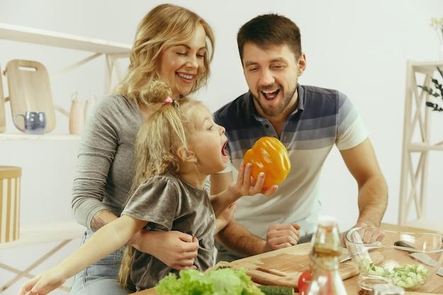 かわいい女の子と彼女の美しい両親は、自宅のキッチンでサラダを作りながら野菜を切って笑っています