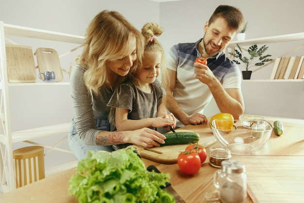 Милая маленькая девочка и ее красивые родители режут овощи и улыбаются