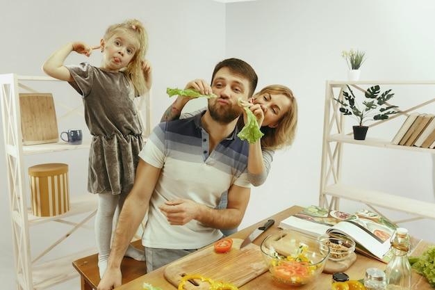 かわいい女の子と彼女の美しい両親は野菜を切っています