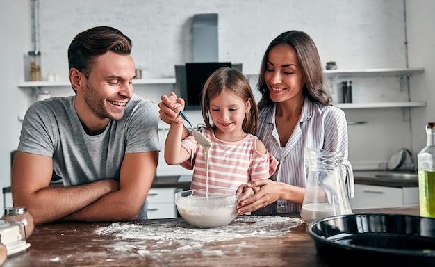 귀여운 소녀와 그녀의 아름다운 부모는 부엌에서 요리하는 동안 베이킹과 미소를 위해 밀가루를 반죽합니다.