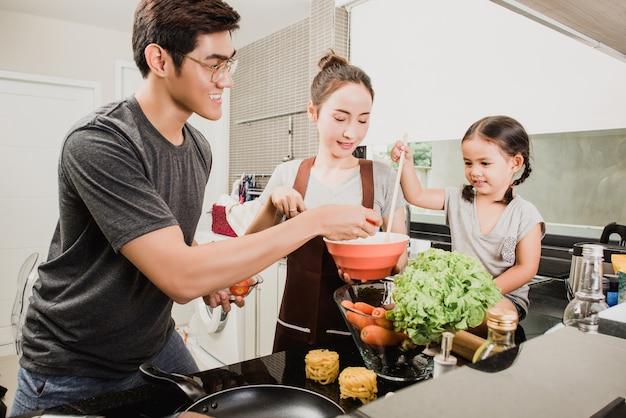 かわいい女の子と彼女の美しい親は、自宅でキッチンで料理中に笑っている