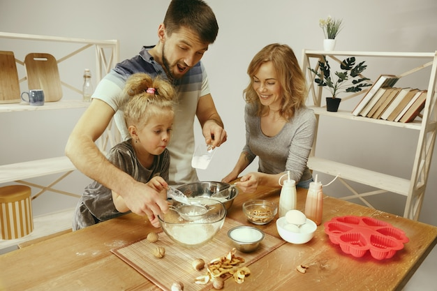 Милая маленькая девочка и ее красивые родители готовят тесто для торта на кухне дома. концепция семейного образа жизни