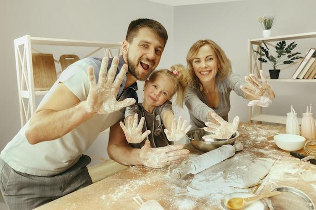 かわいい女の子と彼女の美しい両親は、自宅のキッチンでケーキの生地を準備しています。家族のライフスタイルの概念