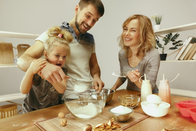 Милая маленькая девочка и ее красивые родители готовят тесто для торта на кухне дома.