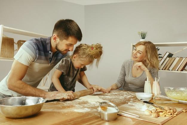 Милая маленькая девочка и ее красивые родители готовят тесто для торта на кухне дома