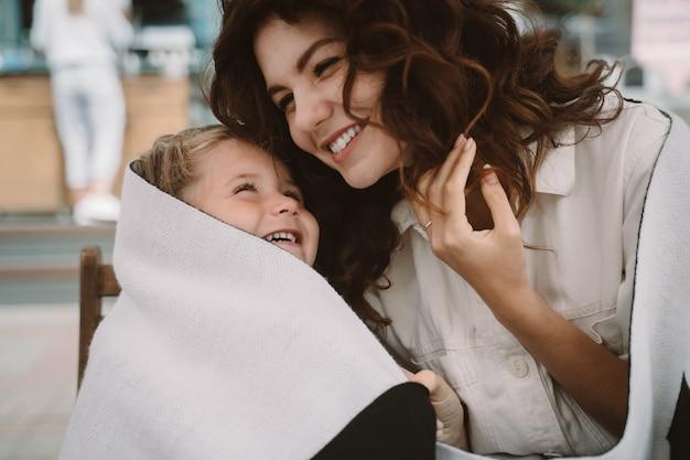 Милая маленькая девочка и ее красивая молодая мама обнимаются на природе