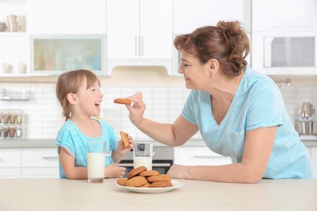 かわいい女の子と彼女の祖母がキッチンでクッキーを味わう