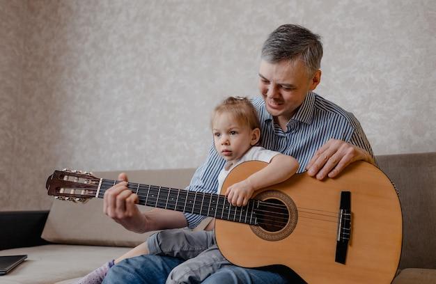 귀여운 어린 소녀와 그녀의 잘 생긴 아버지는 기타를 연주하고 집에서 소파에 앉아 미소. 아버지의 날. 아이들의 보살핌과 교육.