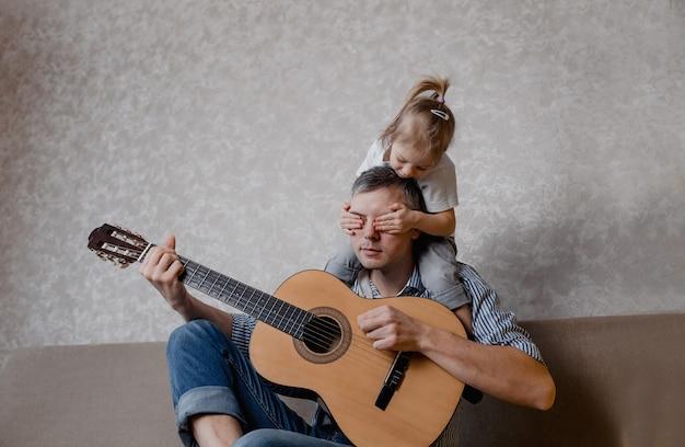 かわいい女の子と彼女のハンサムな父親は、自宅のソファに座ってギターと笑顔を演奏します。父の日。子供の世話と教育。