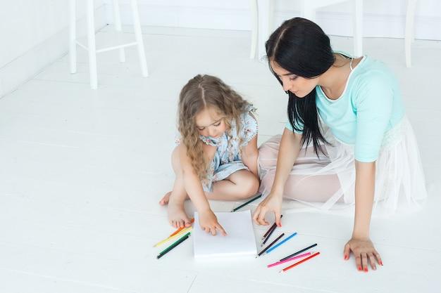 Милая маленькая девочка и ее мать, рисование изображения вместе в помещении.