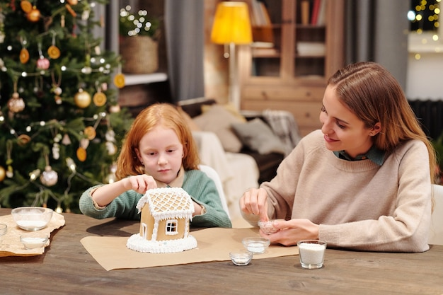 귀여운 소녀와 그녀의 어머니는 축제 디저트를 준비하는 동안 휘핑 크림으로 장식 된 진저 브레드 하우스의 지붕을 뿌리고 있습니다.