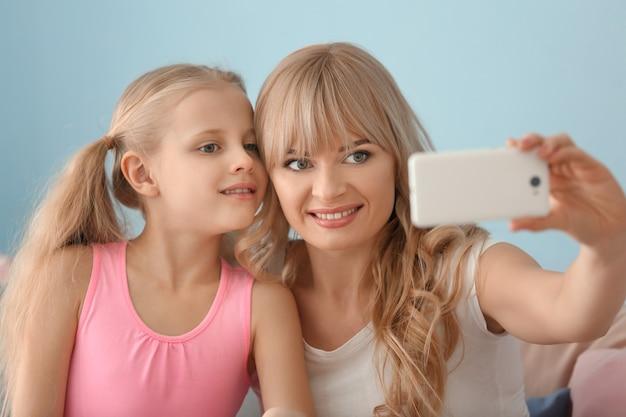 Милая маленькая девочка и ее мать делают селфи дома