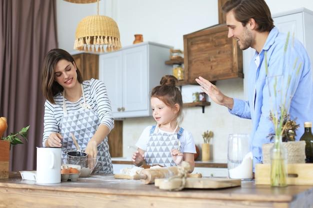 かわいい女の子と彼女の両親は一緒に自宅のキッチンで料理をしながら楽しんでいます。