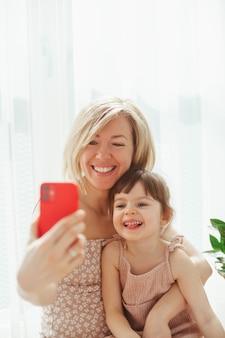 Милая маленькая девочка и ее молодая мать сидят вместе и обнимаются, делают селфи на смартфоне и улыбаются