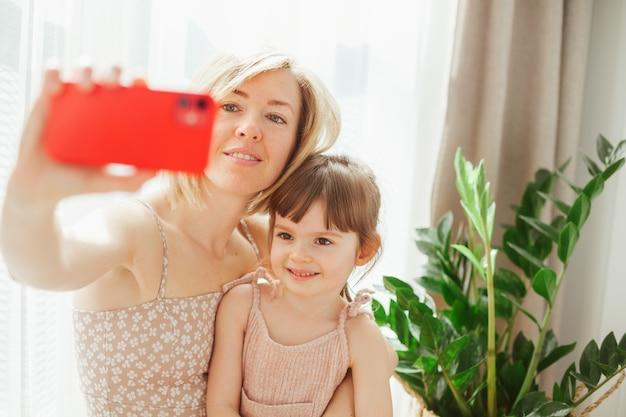 Милая маленькая девочка и ее молодая мать сидят вместе и обнимаются, делая селфи на смартфоне