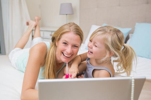 귀여운 소녀와 어머니 노트북을 사용하는 침대에