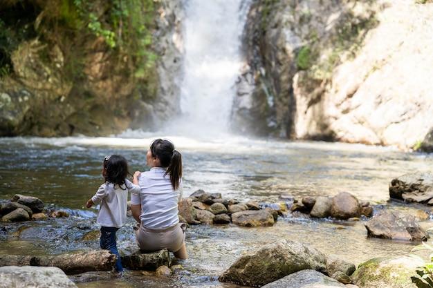 귀여운 어린 소녀와 어머니 물 폭포 폭포 근처에 앉아
