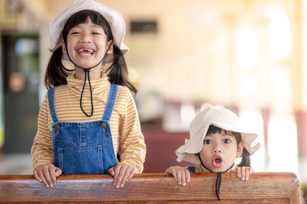 기차에 앉아 있는 귀여운 소녀와 여동생 소년. 두 사랑스러운 행복한 건강한 아이들이 함께 즐거운 시간을 보내고 있습니다. 철도로 가족 휴가를 떠나는 웃는 형제들