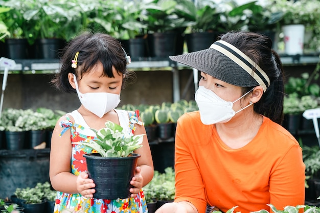 나무 가게에서 식물 화분을 들고 보호용 얼굴 마스크를 쓴 귀여운 소녀와 젊은 아시아 여성