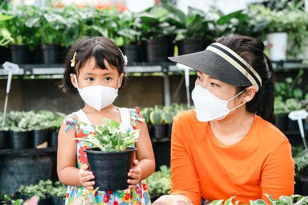 かわいい女の子とツリーショップで植木鉢を保持している保護フェイスマスクを身に着けている若いアジアの女性