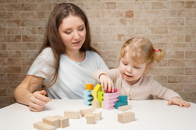 テーブルの上の積み木木のおもちゃで遊ぶかわいい女の子と若い母の女性