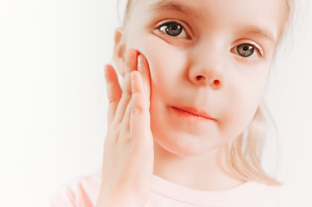 Cute little girl applying cream to her face. skin protection concept