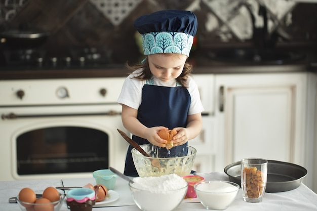 Cute little girl in an apron and a chef's hat breaks an egg into a dish