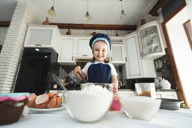 A cute little girl in an apron and a chef's hat is stirring the dough with a wooden spatula