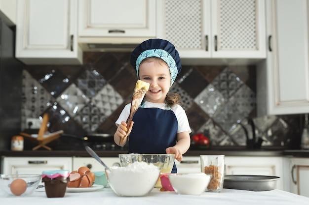 Cute little girl in an apron and a chef's hat is stirring the dough with a wooden spatula