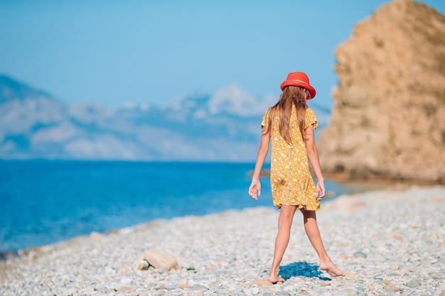 Милая маленькая девочка на пляже во время летних каникул