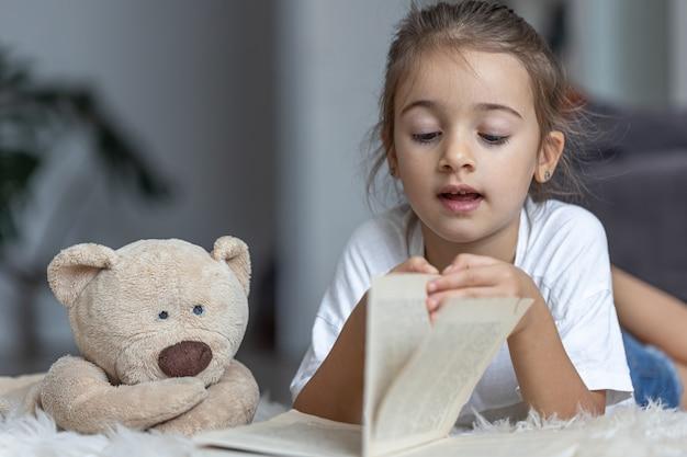 집에 있는 귀여운 소녀가 좋아하는 장난감을 들고 바닥에 누워 책을 읽습니다.